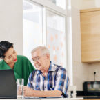 Caregiver helping senior man to figure out how to use laptop for communication with doctor