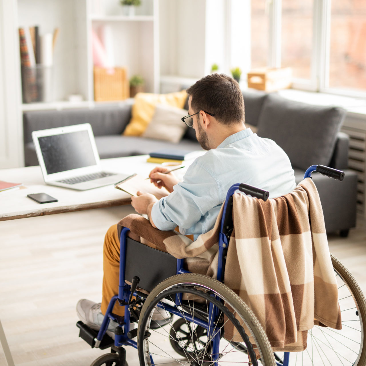Businessman in casualwear making working notes in notepad while sitting in wheelchair at home